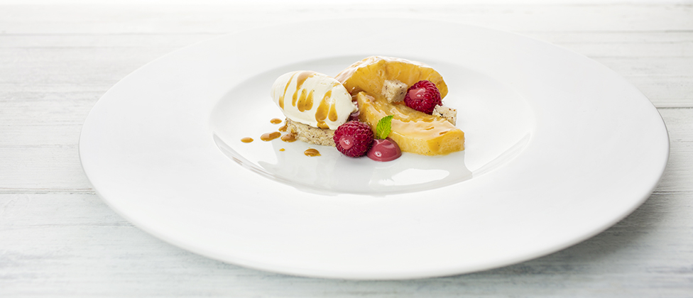 Pineapple with coconut caramel, raspberries and vanilla ice cream